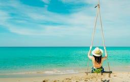 Azjatycki kobiety odzieży swimwear i kapelusz huśtamy się huśtawki przy piaska patrzeć i plażą pięknego tropikalnego raju morze,  zdjęcia royalty free