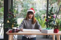 Azjatycki kobiety odzieży Santa Claus kapelusz w domu dziewczyna z notatnikiem, gi Obraz Royalty Free