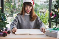 Azjatycki kobiety odzieży Santa Claus kapelusz w domu dziewczyna z notatnikiem, gi Obrazy Stock