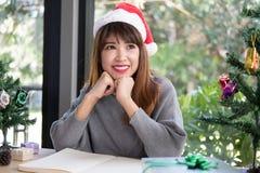 Azjatycki kobiety odzieży Santa Claus kapelusz w domu dziewczyna z notatnikiem, gi Fotografia Stock