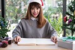 Azjatycki kobiety odzieży Santa Claus kapelusz w domu dziewczyna z notatnikiem, gi Zdjęcie Stock