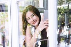 Azjatycki kobiety use smartphone w kawiarnia sklepie Obrazy Royalty Free