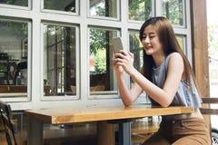 Azjatycki kobiety use smartphone w kawiarnia sklepie Zdjęcia Stock