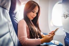 Azjatycki kobiety use telefon komórkowy wśrodku samolotu zdjęcia royalty free
