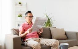Azjatycki mężczyzna czyta gazetę w domu w szkłach Obrazy Royalty Free