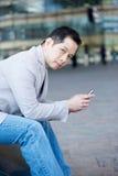 Azjatycki mężczyzna mienia telefon komórkowy Obrazy Royalty Free