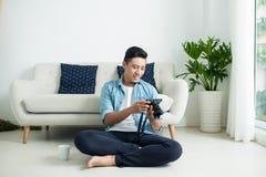 Azjatycki mężczyzna obsiadanie na podłoga i patrzeć kamerę blisko wi obrazy royalty free