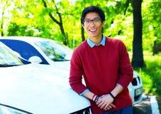 Azjatycki mężczyzna opiera na samochodzie obrazy royalty free