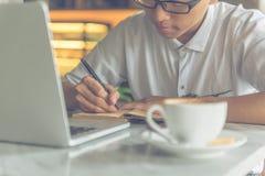 Azjatycki mężczyzna pisze notatkach przy kawiarnią zdjęcie stock