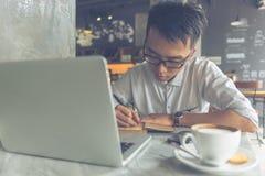 Azjatycki mężczyzna pisze w notatki w białej koszula zdjęcie royalty free