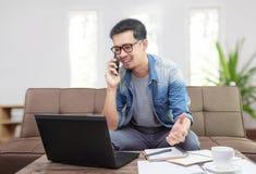 Azjatycki mężczyzna uśmiecha się smartphone opowiada biznes i używa zdjęcia stock