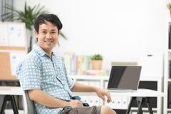 Azjatycki mężczyzna używa laptop w domu, Obraz Royalty Free