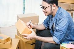 Azjatycki mężczyzna writing adres na pudełku Zdjęcia Royalty Free