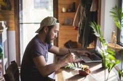 Azjatycki mężczyzna z brodą pracuje na pastylce i laptopie w domu Zdjęcia Stock