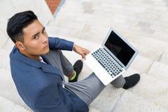 Azjatycki mężczyzna z laptopem na schodkach zdjęcia stock