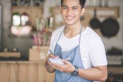 Azjatycki męski kelner w fartucha writing rozkazie obraz stock