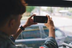 Azjatycki męski turysta fotografuje miasto od okno fotografia royalty free