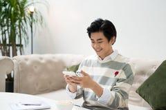 Azjatycki męski uczeń texting telefonem podczas gdy siedzący przy kawiarnią sh Zdjęcia Stock