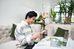 Azjatycki męski uczeń texting telefonem podczas gdy siedzący przy kawiarnią sh Zdjęcie Royalty Free