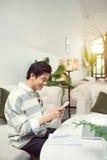 Azjatycki męski uczeń texting telefonem podczas gdy siedzący przy kawiarnią sh Obrazy Stock