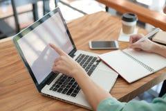 Azjatycki męski writing na notatniku podczas gdy używać laptop Obrazy Stock