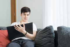 Azjatycki młodego człowieka główkowanie i Zastanawiać się Podczas gdy Pisać papierze przy Zdjęcia Royalty Free