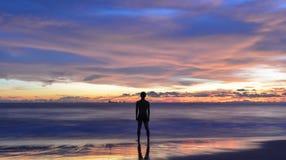 Azjatycki młody człowiek stoi wciąż na plaży gdy zmierzch obraz stock