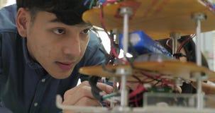 Azjatycki młody elektronika inżyniera budynek, naprawianie robotyka w laboratorium zdjęcie wideo