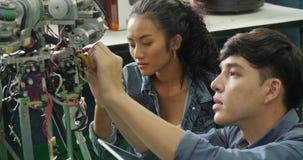 Azjatycki młody elektronika inżyniera budynek, naprawianie robotyka w laboratorium zbiory wideo