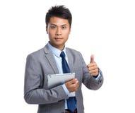 Azjatycki młody biznesmena chwyt z pastylka komputerem osobistym up kciukiem i Obrazy Royalty Free