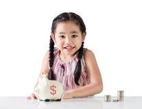 Azjatycki małej dziewczynki oszczędzania pieniądze w prosiątko banku pojedynczy białe tło Obrazy Royalty Free
