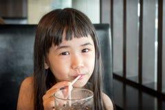 Azjatycki małej dziewczynki popijanie na słomie od szkła Lukrowy Bevera obraz stock