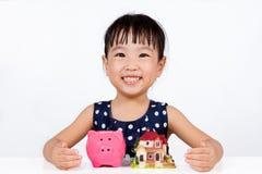 Azjatycki Mały Chiński dziewczyny oszczędzania pieniądze dla Majątkowego pojęcia obrazy royalty free