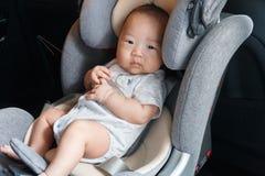 Azjatycki mały dziecko przymocowywał z ochrona paskiem w zbawczym samochodowym siedzeniu obraz stock