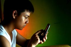 Azjatycki nastolatek używa telefon komórkowego lub smartphone Zdjęcie Royalty Free