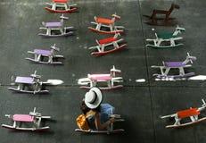 Azjatycki nastolatek w mody sukni siedzi na kolorowym drewnianym koniu przy lokalnym spławowym rynkiem, Bangkok, Tajlandia obrazy stock