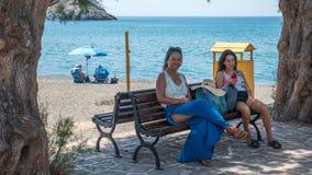 Azjatycki nastoletni i kobieta obsiadanie na ławce przy plażą fotografia royalty free