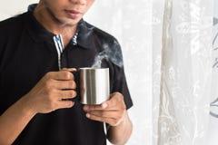 Azjatycki nastoletni mienie kubek z gorącymi napojami w ranku zdjęcia royalty free