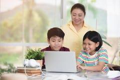 Azjatycki nauczyciel i dzieciaki zabawia używać laptop Fotografia Stock