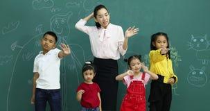 Azjatycki nauczyciel i ucznie macha ich ręki, one stoi przed zieleni ścianą zdjęcie wideo