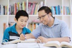 Azjatycki nauczyciel pomaga jego ucznia czytać książkę Zdjęcia Stock