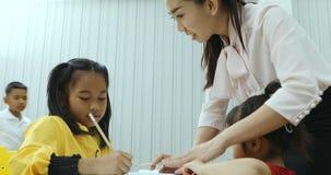 Azjatycki nauczyciel sprawdza ucznia ćwiczenie w klasie zbiory wideo