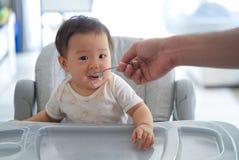 Azjatycki ojciec daje owsiance jego dzieciak na dziecka karmienia siedzeniu obrazy royalty free