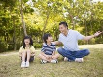 Azjatycki ojciec i dzieci opowiada w parku fotografia royalty free