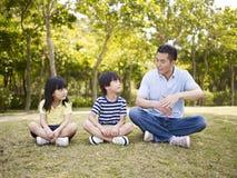 Azjatycki ojciec i dzieci opowiada w parku Zdjęcia Royalty Free