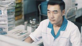 Azjatycki okulista w białej kontuszy cheks obiektywu krzywie na szkłach przy jego pracującym miejscem zbiory