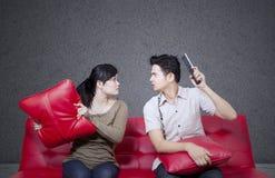 Gniewna pary walka na czerwonej kanapie Zdjęcia Royalty Free