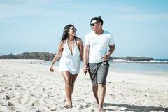 Azjatycki pary odprowadzenie na plaży tropikalna Bali wyspa, Indonezja zdjęcia stock