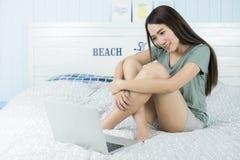 Azjatycki piękno kobiety obsiadanie na łóżku z komputerowym laptopem Obrazy Stock
