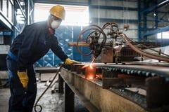 Azjatycki pracownik używa CNC osocza krajacza obrazy stock